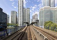 View through the front window of a DLR train leading into the financial district towers of Canary Wharf, London, England.