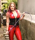 A beautiful 50 year old blond woman wearing latex clothing, holding a whip, looking directly at the camera, outdoors.