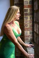 A beautiful 50 year old blond woman wearing latex clothing looking away from the camera.