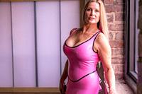 A beautiful 50 year old blond woman wearing latiex clothing looking directly at the camera.