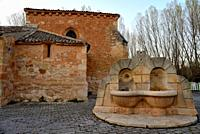 Fountain and church of Santa Maria la Mayor in Peñalba de San Esteban, Soria, Spain.