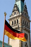 German flag in front of the tower on town hall, Hamburg, Germany.