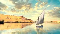 Clouds over river Nile and sailboat in Aswan at sunset.