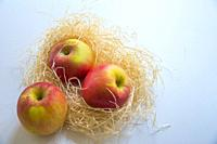 Three apples in a straw nest.