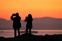 People take photos from Philopappos Hill during sunset.