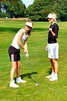 Two girls, golfer, play golf on a golf course in Ystad, Scania, Sweden.