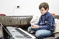 11 year old plays the keyboard at home on the couch.