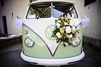Old Volkswagen bus with wedding flowers.