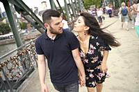 Young couple walking on bridge. Eisener Steg, Frankfurt am Main, Germany.
