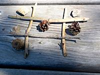 Tris game with sticks and stones, pine cones.