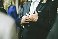 Grooms hands while touching the wedding ring.