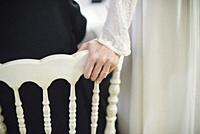 Bride´s hand with ring resting in chair.