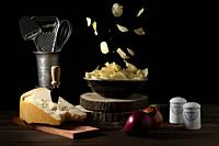 Potato chips falling in a bowl on a table with parmesan cheese, onions, salt and pepper - Dark mood.