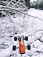 1970's red metal miniature toy racing car and driver on snow covered tree branch in snowy landscape, Sweden