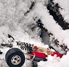 1970's miniature red metal toy racing car and driver depicting a crash in snow and ice, Sweden