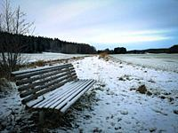 Ice and frost covered frozen bench seat in snow covered landscape, Sweden