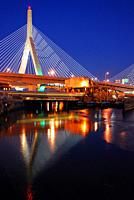 The Zakim Bridge is illuminated and reflected in the Charles River.