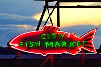 A neon fish is attached to the roof of Seattleâ. . s Pike Place Market, home of the famous fish market.
