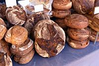 Freshly baked rustic rye granary bread on a food market stall.