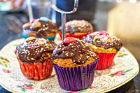 Chocolate covered cupcakes, with sprinkles on top.