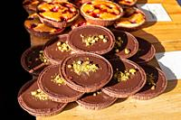 Chocolate and pistachio tarts on display on a market stall in the UK.