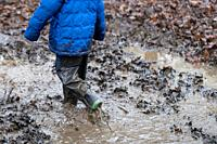 Young children playing in a muddy puddle.