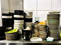 Tilburg, Netherlands. Multiple stacks of dirty disches to be cleaned and washing inside a restaurant's kitchen.