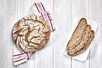 Loaf of rye bread and three slices on a white wooden background.