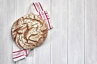Loaf of rye bread on a white wooden background.