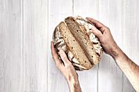 Hands holding a loaf of rye bread split in half on a white wooden background.