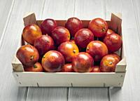 Blood oranges in a wooden box on a white background.