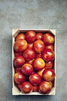 Blood oranges in a wooden box on a grey textured background.