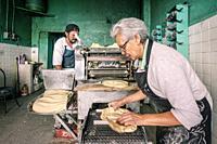 Workers producing corn tortillas in Tortilleria shop in Mexico City.