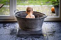 Baby boy having fun in a metal bath tub with bubbles.