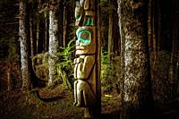 Totem pole beside tourist trail in Sitka National Historical Park in Sitka, Alaska, USA.