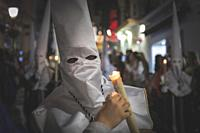 Nazarene in a procession at the holy week in Marbella with a candle.