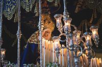 Virgen Maria in procession in Marbella at the holy week , candles an throne at night in Spain.