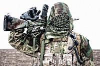 Army marksman, airsoft player in camouflage uniform and load carrier, masking cape on head, armed service rifle with optical sight, hiding face with s...
