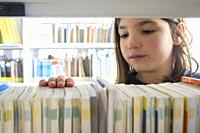 Young girl selecting books from library bookshelf. Children creativity and imagination concept.