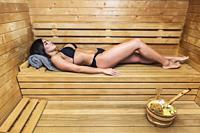 Young brunette lying alone on wooden shelf in steam room and relaxing.