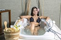 Sensual young brunette in bikini lying in recreation bath enjoying massage center.