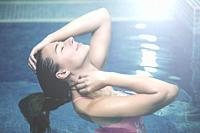 Horizontal indoors shot of young girl with eyes closed adjusting hair and relaxing standing in swimming pool.