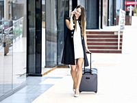 Charming trendy woman in elegant outfit walking with suitcase at street and talking phone.