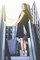 Back view of young stylish businesswoman with luggage on moving stairs looking at camera over shoulder.