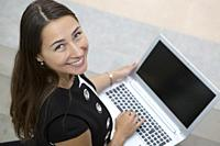 From above shot of young cheerful businesswoman posing with laptop and looking at camera.