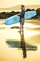 Side view of man holding surfing board and standing on wet sand reflecting sunset light. .
