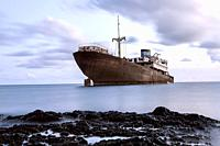 An old metal ship has frozen into the ice. Horizontal outdoors shot.