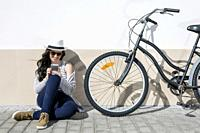 Young cheerful woman in sunglasses and hat sitting nearby bike and using device. Lanzarote, Gran Canaria, Spain.