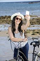 Young smiley woman in hat and sunglasses with bike getting selfie on seaside of Gran Canaria, Spain.