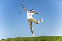 Bright excited brunette in sportswear jumping happily with golf driver in hands above green lawn on blue sky.